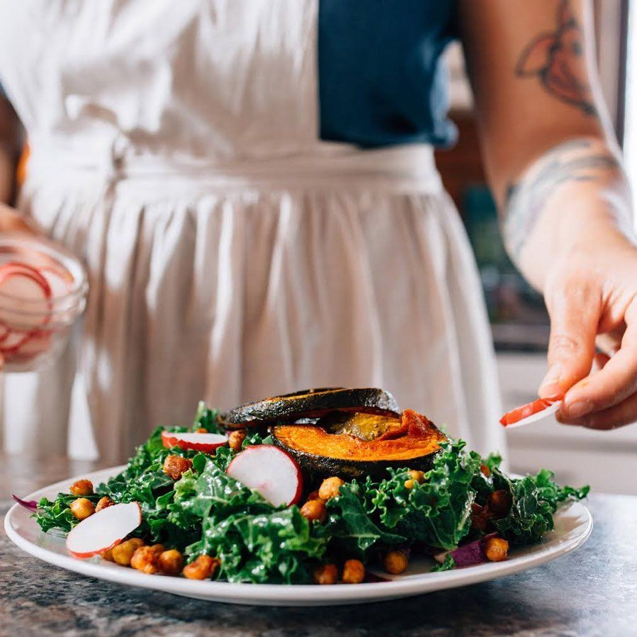A close up side view of a plate of bright green kale and orange squash salad. The arms and torso of a light brown skinned-person with tattoos are visible as they plate the food