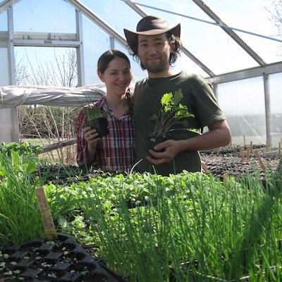 Farmers Alex & Kim of Mulberry Moon farm stand smiling in their hoop house in front of trays of green seedlings