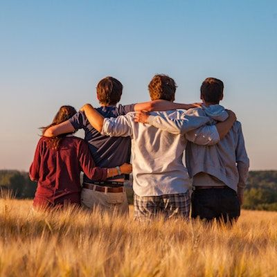Group of people in a field with arms around each other