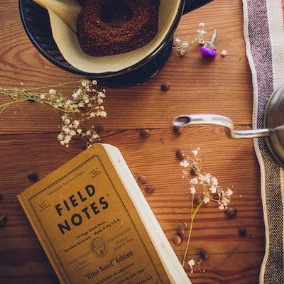 Field notebook with coffee on table