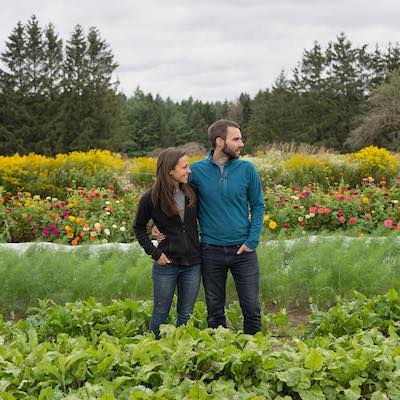 Farmers Paula & Dave stand in their vegetable field at Salad Days Farm